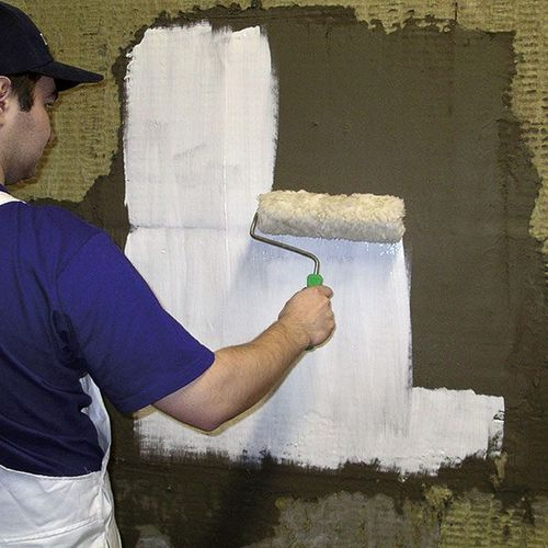 Обработка стены грунтовкой